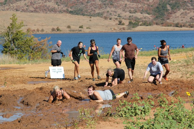 Competitors crawl through the mud, one of several obstacles, in the Run Amok challenge Oct. 1 at Lake Elmer Thomas Recreation Area.