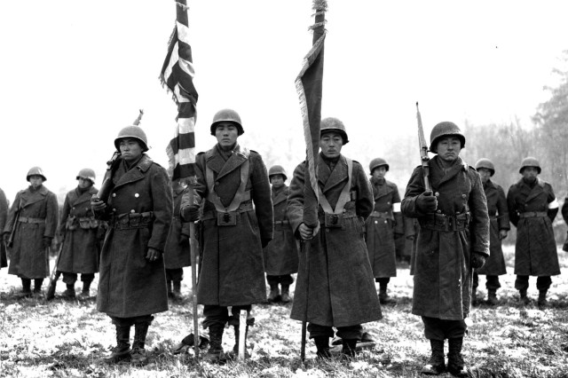 Two color guards and color bearers of the Japanese-American 442d Combat Team, stand at attention, while their citations are read. They are standing on ground in the Bruyeres area, France, where many of their comrades fell.