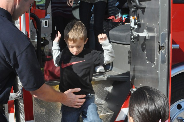 "Lincoln Elementary student Alexander Carrier, 5, is helped down from a fire truck during Fire Prevention Week as Hannah Woodall, 10, Lauren Bourcher, 7 and Kassi Woodall, 8 look on. ""Sitting in that fire truck was awesome,"" Carrier said. Photo by Glen Paddie, Fort Campbell Courier staff."