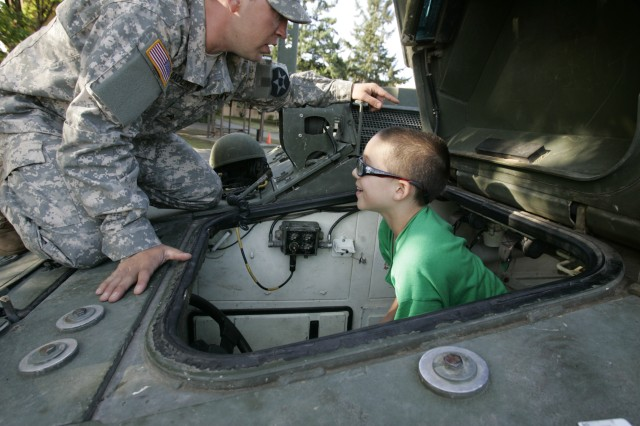 Sgt. Christopher Spradlin explains the vehicle driving system to 10-year-old Alex Papale.