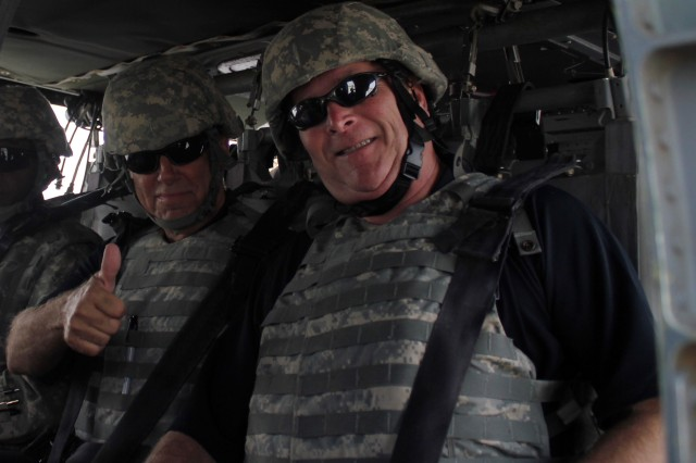 Col. (Ret.) Danny McKnight, whose character was portrayed in the movie Black Hawk Down, gives the thumbs up as a UH-60 Black Hawk helicopter from the 1st Air Cavalry Brigade, 1st Cavalry Division takes off Oct. 4. McKnight, along with Charlie Manis, who is sitting to his left, Max Mullen, and Keni Thomas, was part of the Rangers Tour, which is American 300's first warrior tour that highlights profiles in extreme courage. McKnight was the commander of a ground convoy during the battle of Mogadishu in Somalia on Oct. 3, 1993. (U.S. Army photo by Staff Sgt. Joe Armas)