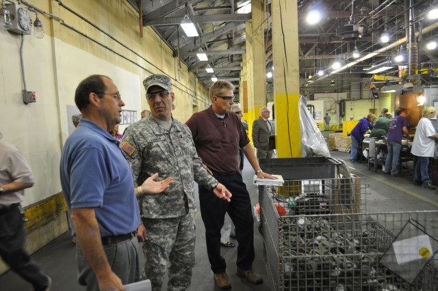 Brig. Gen. Gustave F. Perna, commanding general, Joint Munitions Command, gets briefed while touring an ammunition production line at Iowa Army Ammunition Plant in Middletown, Iowa.