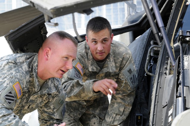 Chief Warrant Officer Michael Fresenburg, Charlie Co., 1st Attack Recon Battalion, 3rd Aviation Regiment, shows the gunner's seat of the AH-64 Apache to 1st Lt. Chris Jackson, Echo Co., 3rd Battalion, 69th Armor Regiment, at Hunter Army Airfield, Sept. 30.