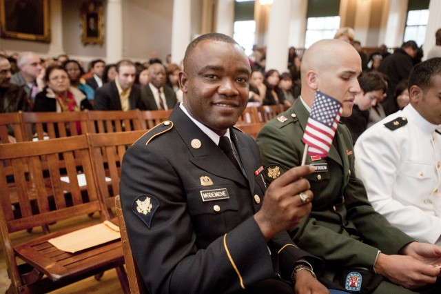Spc. Anthony Mgbemene of the Natick Soldier Systems Center waves a small American flag prior to becoming a U.S. citizen Oct. 6 at Faneuil Hall in Boston.