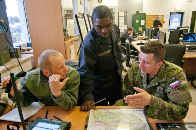 Dressed in 'enemy uniform,' 1st Lt. Victor Abiona from U.S. Army Europe's 1st Battalion, 4th Infantry (center) discusses opposing forces operations with his Slovak counterparts Sgt. Branislav Czibor (left) and Capt. Radomir Botka, at the 1-4th Tactical Operations Center during the 173rd Airborne Brigade Combat Team's Full-Spectrum Training Exercise at Hohenfels, Germany, Oct. 7, 2011.