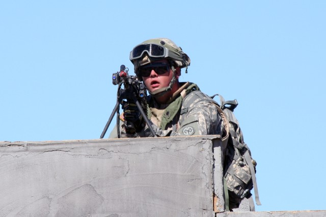 """NATIONAL TRAINING CENTER, FORT IRWIN, Calif. """" A New York Army National Guard Soldier from C Troop, 2nd Squadron, 101st Cavalry provides overwatch from a rooftop for fellow troops maneuvering through a mock village here Oct. 9 during training. The NTC training rotation, through late October, provides Soldiers from the 27th Infantry Brigade Combat Team with a realistic, demanding training environment. The exercise stresses leaders, Soldiers and staffs in a simulated combat environment.  The unit, based in Buffalo, N.Y., is part of the 27th Infantry Brigade Combat Team, training here as part of its preparations for mobilization and deployment to Afghanistan in early 2012. About 1,500 of the Soldiers are currently scheduled to deploy.  U.S. Army photo by Lt. Col. Richard Goldenberg, NY Army National Guard. (RELEASED)"""