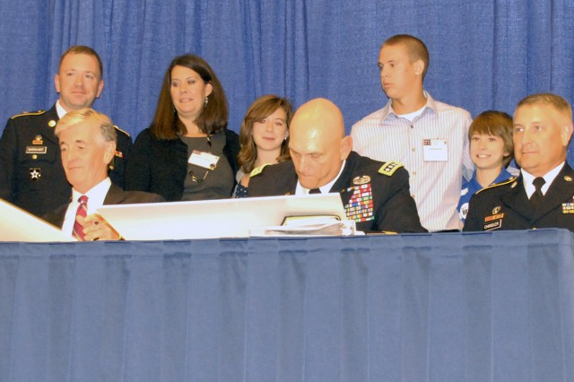 Secretary of the Army John McHugh, Chief of Staff of the Army Gen. Raymond T. Odierno and Sgt. Maj. of the Army Raymond F. Chandler III sign the Army Family Covenant, Oct. 10, 2011, as wounded warrior Sgt. Jeremy Barnhart and his family look on. The Barnhart family was honored as the Association of the United States Army volunteer family of the year.