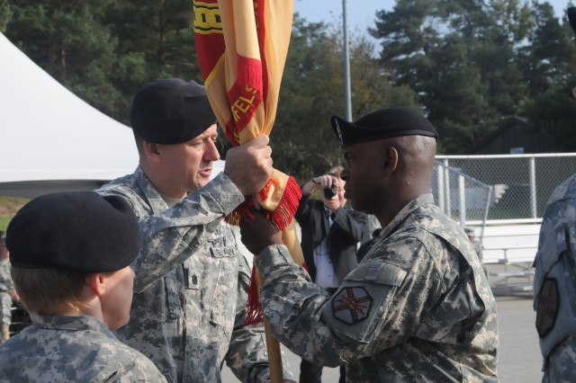 Command Sgt. Maj. Kenneth McKoy (right) accepts the guidon from U.S. Army Garrison Hohenfels Commander Kevin J. Quarles at the change of responsibility ceremony.