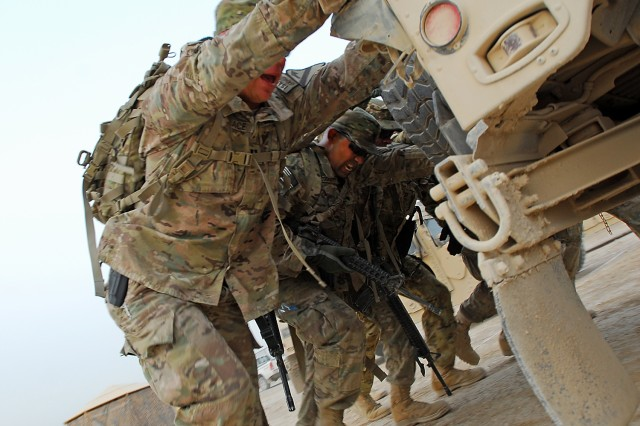 CAMP MARMAL, Afghanistan -- Soldiers assigned to the 1st Air Cavalry Brigade, 1st Cavalry Division push a Humvee during a joint spur ride Oct. 6. The Soldiers' spouses back at Fort Hood also took part in a spur ride as well that was staged by the brigade's rear-detachment. (U.S. Army photo by Sgt. Richard Wrigley)