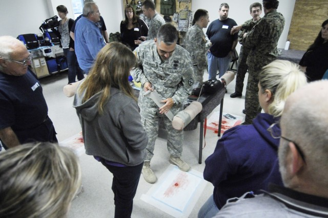 Capt. Martin Stewart, officer in charge at the Medical Simulation Training Center on Fort Drum, N.Y., shows civilian emergency medical services workers how to apply a bandage during a medical skills lab Sept. 29, 2011.
