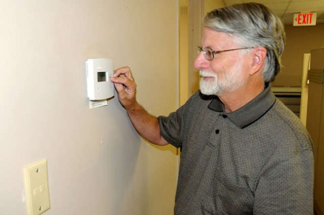 Buddy Coleman, Fort Rucker energy engineer, adjusts a digital thermostat at the DPW building to save energy. Coleman is helping with the organization of the first-ever Energy Expo to be held at the Fort Rucker Festival Fields Oct. 20.