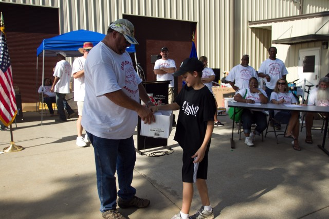 Prizes abounded during Anniston Army Depot's Employee Appreciation Day Oct. 6. Here, Shannon Steward, a depot retiree, enlists the aid of one of the many children at the event to find out the next winner.