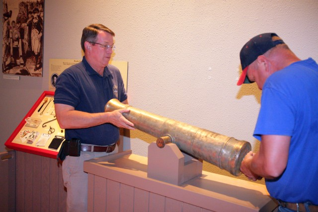 Gordon Blaker and Zane Mohler, Field Artillery Museum director and exhibit specialist respectively, lift a three-pounder infantry support cannon captured during the Revolutionary War. The artillery piece is located in the museum's South Gallery.