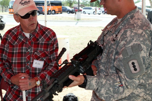 Drill Sergeant (Staff Sgt.) Patrick Zellner, A Battery, 1st Battalion, 40th Field Artillery, shows Vietnam veteran Mike Stephens the M249 squad automatic weapon at the Fort Sill Artillery Museum on Oct. 5. Stephens said it would have been a good weapon to have in Vietnam.