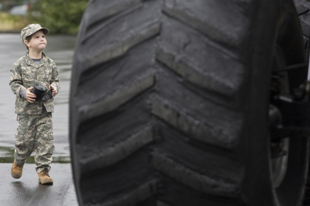 Four-year-old Max Huffmann is dwarfed by one of Bigfoot's tires before it crushed two trucks at the Exchange parking lot Oct. 7, at Joint Base Lewis-McChord, Wash.