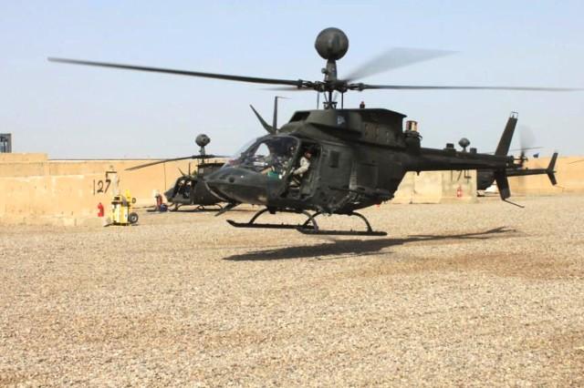 An OH-58 Kiowa Warrior prepares to park on the newly graded and graveled air strip at Camp Taji, Iraq, Sept. 29, 2011.