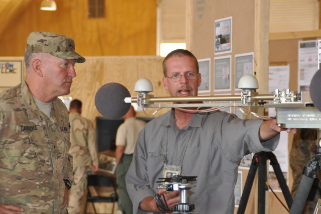 """Doug McCleary, field service representative for the U.S. Army Unattended Transient Acoustic MASINT Sensor system, speaks with Brig. Gen. Les J. Carroll, Joint Sustainment Command""""Afghanistan commander at the Electronic Sustainment Support Center""""Kandahar open house held Oct. 8."""