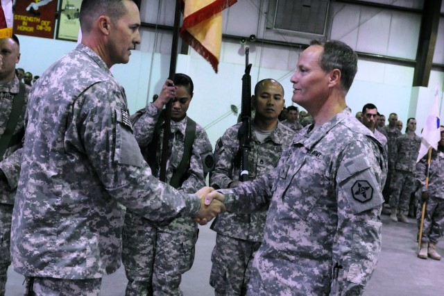 Brig Gen. Jonathan G. Ives, right, and Command Sgt. Maj. Thomas Jennings, the 364th Expeditionary Sustainment Command's commanding general and command sergeant major, shake hands after uncasing their colors, symbolizing that the 364th ESC is operational at Camp Arifjan, Kuwait during a flag unfurling ceremony, Oct. 6, 2011. (Photo by Cpl. Christopher Bigelow, 364th ESC.)
