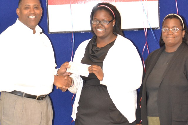 Seventeen year-old Jasmine Gilmore earns a $2,000 reward, Oct. 5, because she maintained a high grade average. She stands with her mother Beverly Carradine-Gilmore and Main Exchange store manager, Donald Basil.