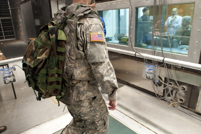 Researchers monitor a Soldier while he walks on a treadmill in the Doriot Climatic Chambers at Natick Soldier Systems Center.