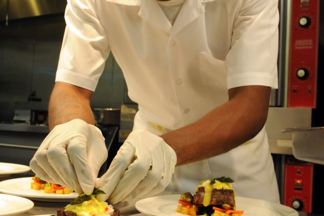 """FAYETTEVILLE, N.C. """"  Pfc. O'Brian Palmer  deftly adds asparagus tips to the main course of char grilled """"Oscar"""" filet mignon topped with lump crab salad and glazed vegetables on a bed of wilted spinach, for the guests of the Soldier Luncheon held 14 Oct. at the Highland Country Club.  Palmer, a food service specialist for 3rd Brigade Combat Team, 82nd Airborne Division, and recent winner of the XVIII Airborne Corps and Fort Bragg 2011 best chef competition, helped design the menu and prepare the courses.Photo by Sgt. Christopher Harper, 3BCT, PAO (Released)"""