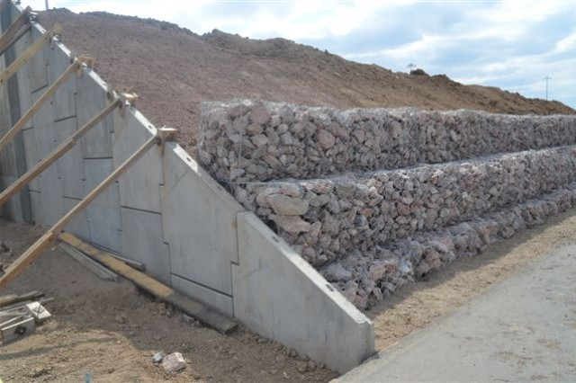 A rock retaining wall is installed to keep the dirt covering the Energetics Service Magazine from washing into the roadway.