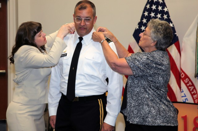 Col. Clark W. LeMasters' daughter Lauren (left) and mother Faye (right) help him put on his new rank of brigadier general during a ceremony Oct. 18.