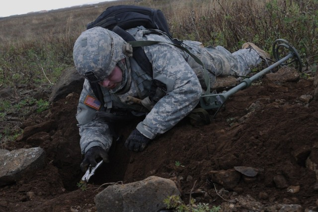 "Sgt. Jeremy Rininger, a team leader with the 21st Theater Sustainment Command's 702nd Explosive Ordnance Disposal Company, 18th Combat Sustainment Support Battalion, 16th Sustainment Brigade, based in Grafenwoehr, Germany, dismantles a buried improvised explosive device Oct 5, 2011, during the North Atlantic Treaty Organization's annual EOD exercise ""Northern Challenge"" which was hosted by the Icelandic Coast Guard at Naval Station Keflavik, Iceland."