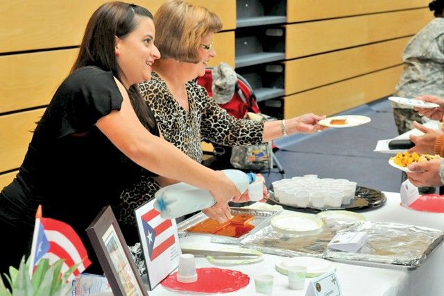 Capt. Laiza Correa and her mother, Lavinia Davila, serve Puerto Rican eggnog and flan during Wiesbaden's Hispanic Heritage Month Celebration.