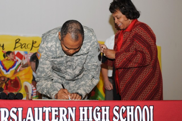 Brig. Gen. Aundre F. Piggee, the commanding general of the 21st Theater Sustainment Command, signs a new proclamation with Kaiserslautern High School Principal Jennifer Beckwith as a part of the Hispanic Heritage Month celebration held at the Galaxy Theater on Vogelweh, in Kaiserslautern, Germany, Oct. 14.
