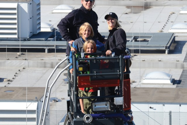 USAG Stuttgart firefighter Manfred Hees takes Dana Wharton and her children, Rhianna (in blue) and Riley, high above the Exchange in the rescue bucket of the fire department's new aerial ladder truck.
