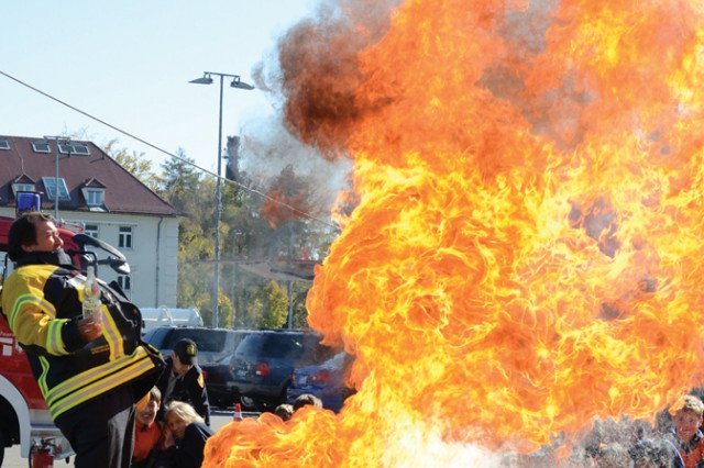 A fireball shoots out as Nico Mayan, the Böblingen Youth Fire Department leader, demonstrates what happens when water is thrown onto a grease fire, during USAG Stuttgart's Fire Prevention Day held outside the Panzer Exchange Oct. 15.
