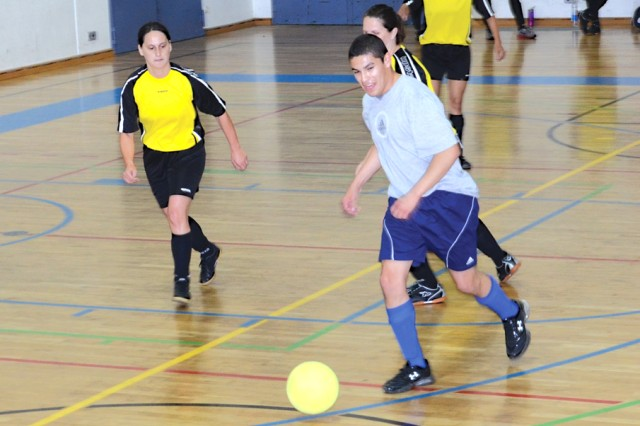 Miguel Angel (in gray T-shirt) forward for the Patch Clinic indoor soccer team, has control of the ball against the MWR all-women's team, the Honey Badgers, during a game on Oct. 6 in the Panzer Fitness Center gymnasium.