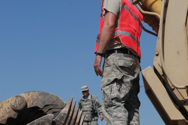 Sgt. Darryl Frees, 227th Quartermaster Compnay, performs a final inspection on an excavator he has loaded onto a flatbed truck at Camp Liberty, Iraq. The 402nd Army Field Support Brigade operates seven turn-in facilities in Iraq to assist units going home.