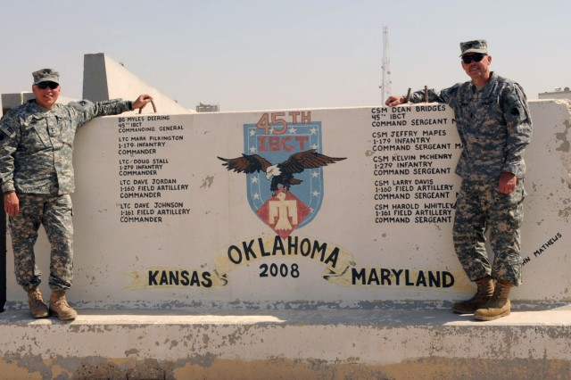 CAMP BUEHRING, Kuwait - Maj. Gen. Myles L. Deering, Oklahoma Adjutant General and Norman, Okla. native and Command Sgt. Maj. Steven Jensen, Okla. Command Sgt. Maj., pose next to a concrete barrier painted with their unit's crest here Oct. 17. Third Army's commitment to the well-being of its troops remains a priority. Through morale-building visits such as Maj. Gen. Deering's visit to Camps Buehring and Virginia, Third Army is helping to inspire, educate and inform Servicemembers, the strength of our nation.