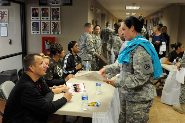 Sgt. Jessica Waters of the 3d Sustainment Command (Expeditionary), asks Jeff Walz, head coach of the University of Louisville women's basketball team, for an autograph during the team's visit to Fort Knox. While at Fort Knox, the team took on Dunagan Teamwork Development Course and visited the 3d ESC headquarters where they signed autographs for unit members and their families. (U.S. Army photo by Staff Sgt. Michael Behlin)