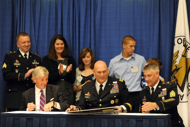 Hon. John McHugh, Secretary of the Army, Army Gen. Raymond T. Odierno, Chief of Staff of the Army, and Sgt. Maj. Raymond F. Chandler III, Sergeant Major of the Army, sign the Army Family Covenant during the Military Family Forum at the 2011 Association of the United States Army Annual Meeting and Exposition in Oct. 10, 2011 in Washington, D.C.