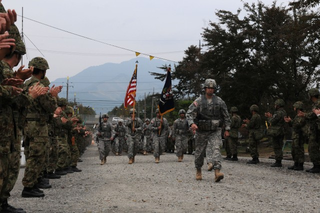 Soldiers of the 3rd Battalion, 141st Infantry Regiment, headquartered out of Weslaco, Texas, marched onto Kita-Fuji Training Area, Japan, as Japan Ground Self-Defense Force soldiers applauded their entrance to the bi-lateral Orient Shield exercise between the two forces on Oct. 11, 2011. The annual Orient Shield exercise is designed to strengthen military operations and ties between United States forces and the JGSDF.