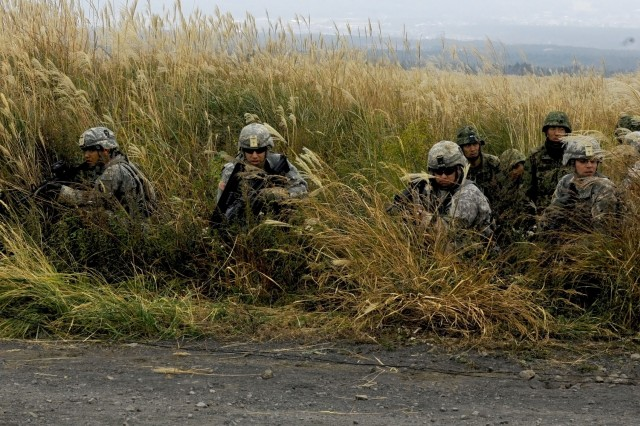 Soldiers with 3rd Battalion, 141st Infantry Regiment, out of Weslaco, Texas, kneel down and survey the terrain for the enemy as soldiers with the 1st Division, Eastern Army, Japan Ground Self Defense Force watch and learn the tactics of the squad live fire exercise at Nashigahara Barracks, in Kita-Fuji Training Area in Yamanashi Prefecture, Japan, Oct. 14, 2011. Soldiers and JGSDF members are part of Orient Shield 11, which consists of a tactical level, field training exercise.