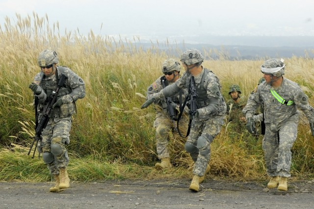 Soldiers with 3rd Battalion, 141st Infantry Regiment, out of Weslaco, Texas, run through a grassy field during a squad movement exercises as the 1st Division, Eastern Army, Japan Ground Self Defense Force members learn and adapt at Nashigahara Barracks, in Kita-Fuji Training Area in Yamanashi Prefecture, Japan, Oct. 14, 2011. The JGSDF and U.S. Army have conducted Orient Shield, which consists of a long history of partnership and increasing interoperability, since it started in 2000.