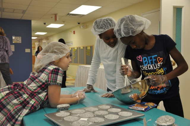 From left, Abigail Sawyer, 8, and Janiya Edmond, 9, watch as Jahara Johnson, 11, stirs muffin batter Tuesday at the Imboden Street School Age Center. The children were among those children baking refreshments for Wednesday's ribbon-cutting ceremony that marked the official opening of the school age center and the new child development center.