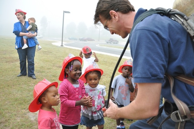 "Shane Morris, with the Fort Jackson Fire Department, shows a group of toddlers fire equipment during a demonstration at the Imboden Street Child Development Center. The CDC, which had a ""soft"" opening in August,  serves as an extended care facility to accommodate the mission requirements of Fort Jackson Soldiers."