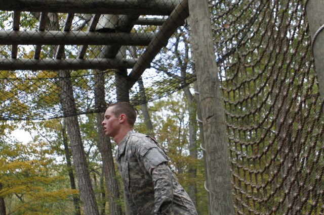 While teammates rope-climb to the top of the obstacle and negotiate across, other cadets conduct lunges while carrying full water canisters. The 4th Regiment conducted its first-ever Stud Mudder on Oct. 15 at Camp Buckner, with nearly 80 teams of cadets working through a series of obstacles throughout a three-mile course. Photo by Mike Strasser, West Point Public Affairs