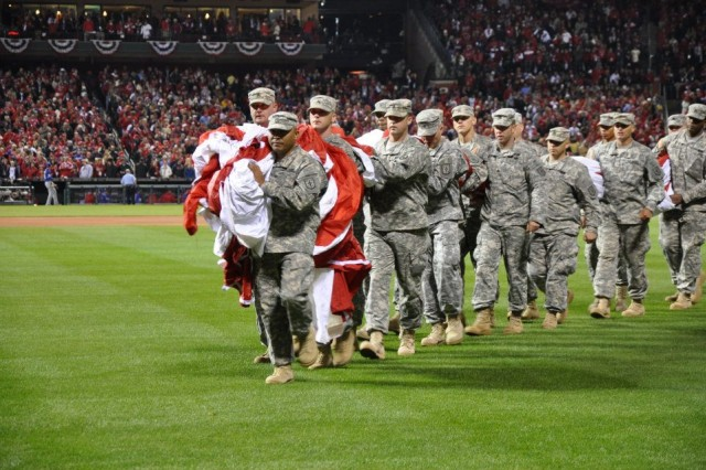 Sgt. 1st Class Zac Fejeran, an air traffic control operator assigned to Headquarters and Headquarters Company, 4th Maneuver Enhancement Brigade, leads Fort Leonard Wood Soldiers off the field after unfurling the Nations colors at Busch Stadium in St. Louis, Mo., during Game 1 of the 2011 World Series Oct. 19, 2011. Major League Baseball dedicated the game between the Texas Rangers and the St. Louis Cardinals to veterans and their families.
