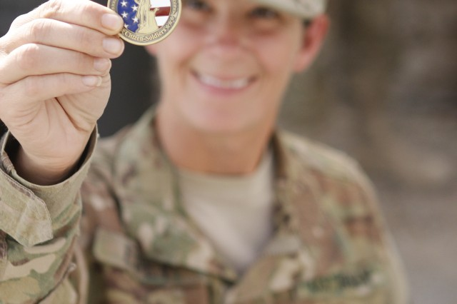 Spc. Kimberly Espey, a member of the 230th Signal Company, holds up her very first coin with pride to show off the special commendation she recevied from Command Sgt. Maj. of the National Guard Richard Burch during his visit to Kandahar Airfield, Afghanistan, Oct. 20, 2011. He paid a special visit to his deployed National Guard Soldiers  to discuss upcoming changes regarding funding and standards.