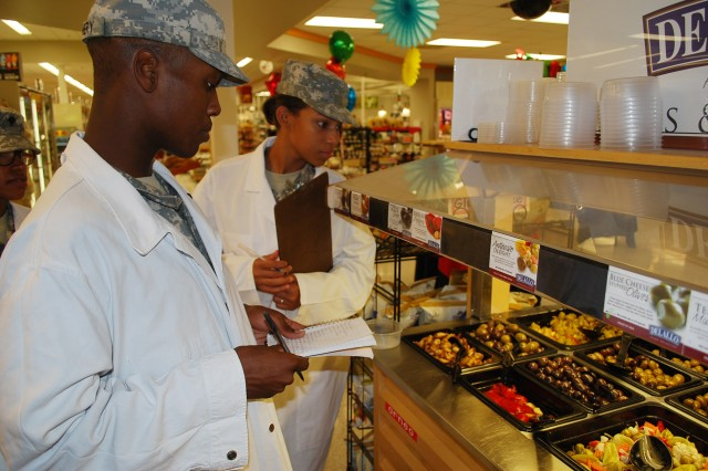 Pvts. J'vonte Gunthery and Destiney Butler ensure ready to eat food at a self-service display in the commissary is safe for consumption.
