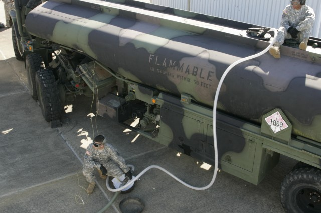 Spc. Charles Gill, left, and Spc. Shaquan Hollaway establishes a fuel flow of JP-8 into a hose from the pumping system to one of  the 593rd Sust. Bde.'s tanker trucks at the JBLM Installation Fuel Filtering Facility Tuesday.