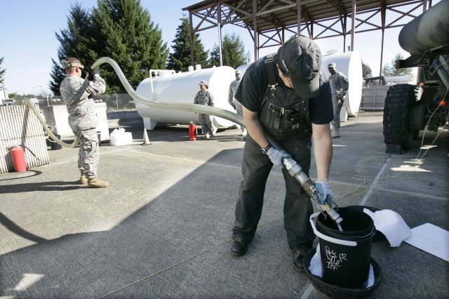 Environmental protection specialist Victor Rodelo empties fuel into a bucket after filing a 593rd Sust. Bde. tanker at JBLM's Installation Fuel Filtering Facility.