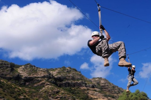 "WAIALUA, Hawaii "" Spc. Hunter Parrot (left), and Spc. Ricky Lee Edwards Jr.(right), Soldiers of 1st Battalion, 21st Infantry Regiment use a zip line to dismount the obstacle course at the YMCA Camp Erdman here, 7 Sept. Soldiers negotiated the obstacle course as a high adrenaline team building and communication exercise."