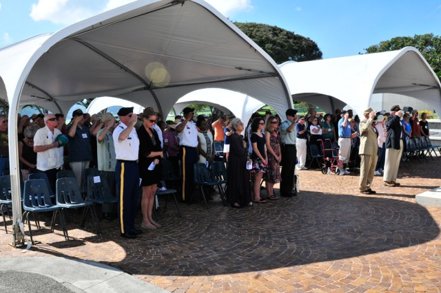"HONOLULU, Hawaii "" Veterans, Soldiers, Family, and friends render honors during the playing of taps while attending the annual 25th Infantry Division Association Memorial Service at the Nation Memorial Cemetery of the Pacific on Oct. 2 here. The memorial service was held in honor of all of the Veterans and Soldiers who lost their lives over the past year."